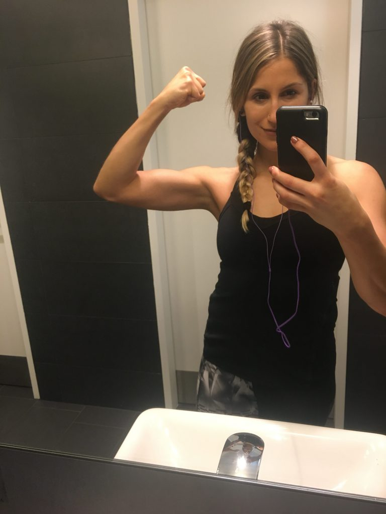 girl flexing biceps in mirror